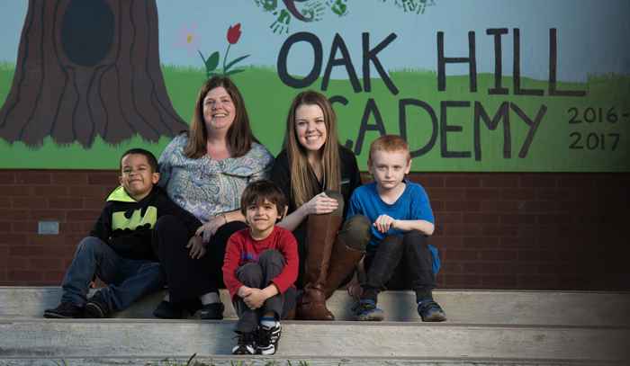 Master of Occupational Therapy student Kayleigh Quinn poses with children from the school where she painted a mural celebrating school spirit.
