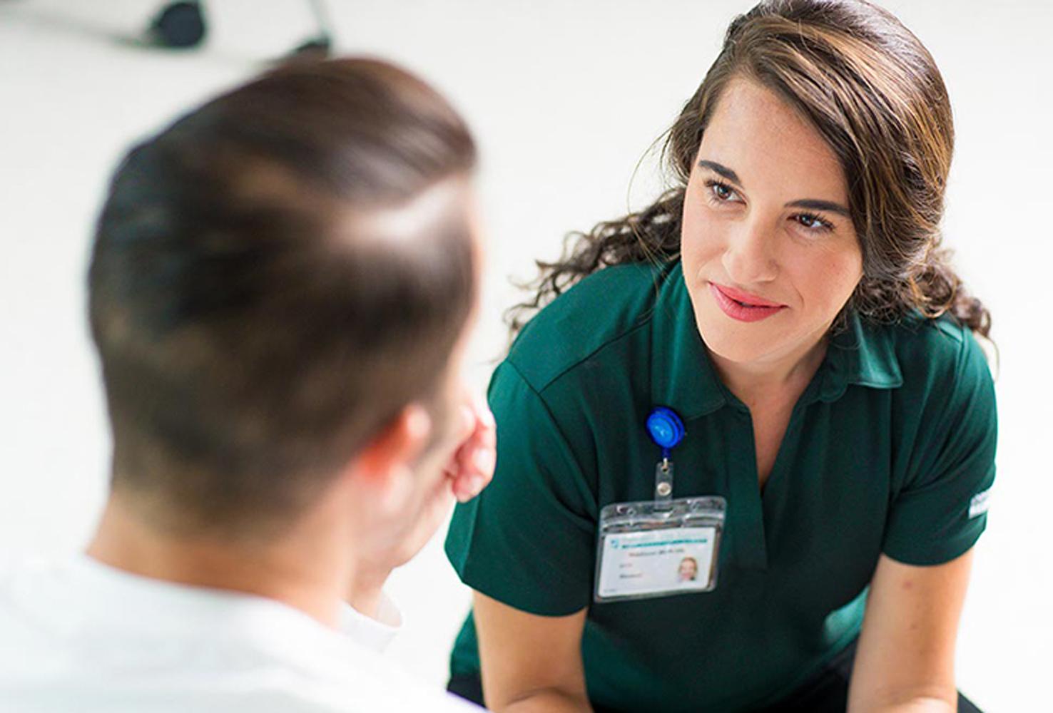 Nurse in a green coat speaking to patient.