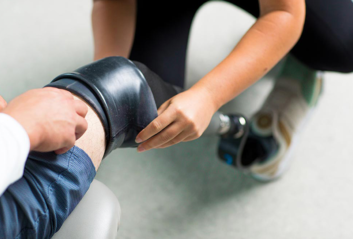 psychical therapist helping patient put on prosthetic leg