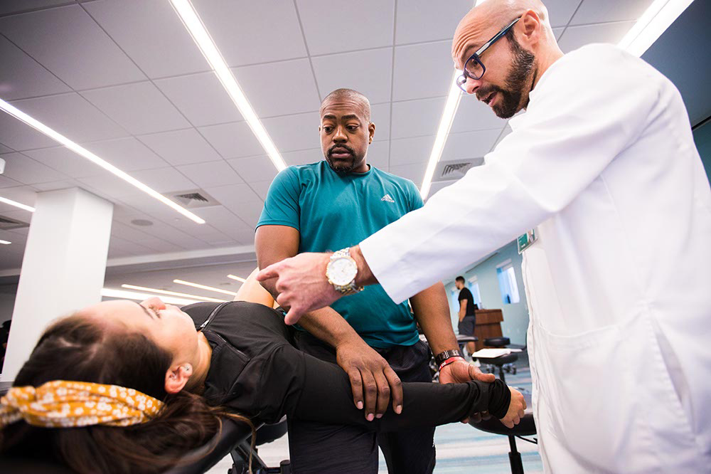 physical therapist leaning over patient.