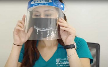Health care worker wearing a face mask and face shield